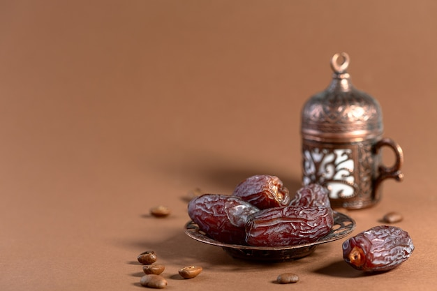 Dried dates are traditional oriental dessert for arabic coffee, a selective focus. monochrome style. copy space.