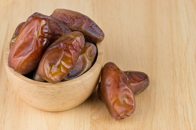 Dried dates in the bowl on the wood table.