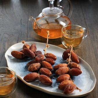 茶色の木製テーブルの上の楕円形のプレート上の乾燥ナツメヤシフルーツ、茶色のテーブルの背景にお茶を添えて