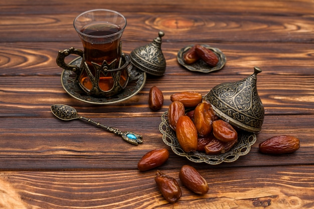 Dried dates fruit on small plate with glass of tea