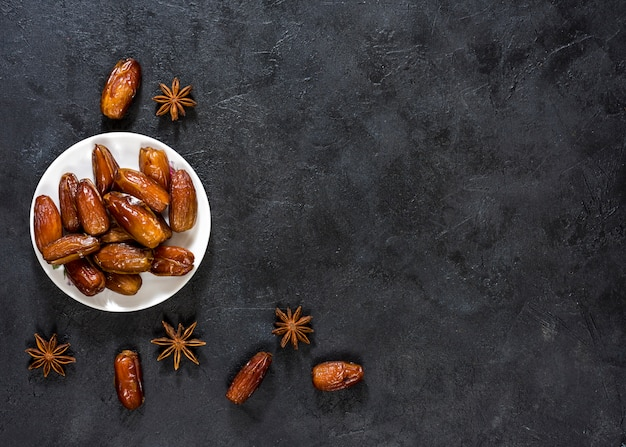 Dried dates fruit with anise on table