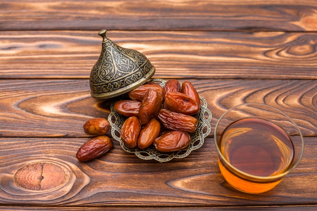 Dried dates fruit with glass of tea on table