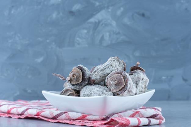 ボウル、ティータオル、大理石のテーブルで乾燥したナツメヤシ。