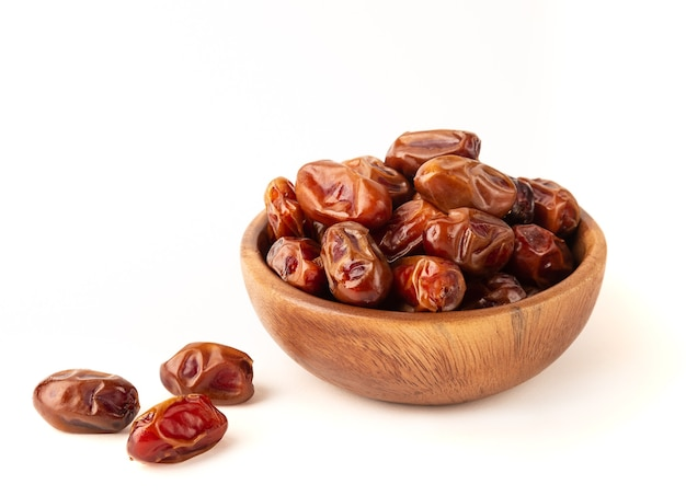 Dried dates in wooden bowl isolated on white background.