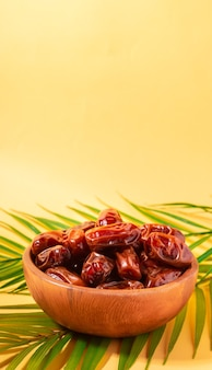 Dried dates in wooden bowl with palm leaves on yellow background. space for text.