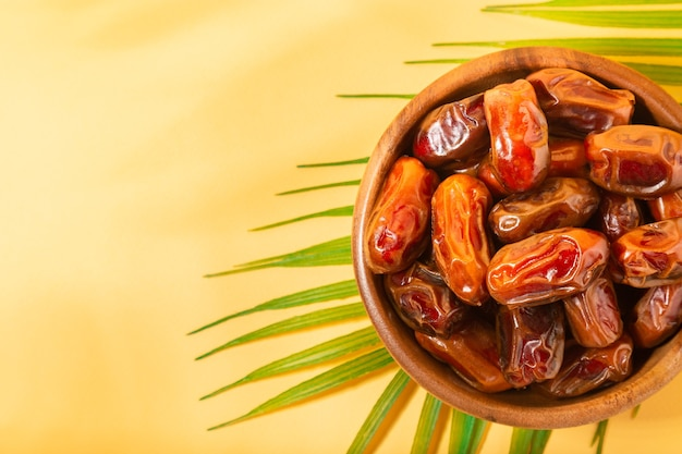 Dried dates in wooden bowl with palm leaves on yellow background. top view. space for text.