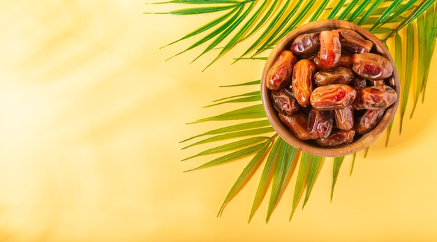 Dried dates in wooden bowl with palm leaves on yellow background with light shadows top view