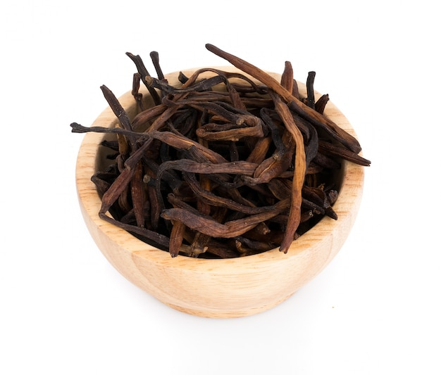 Dried day lily in wooden bowl on white surface