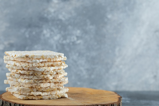 Dried diet crispy rice round bread isolated on wood piece.