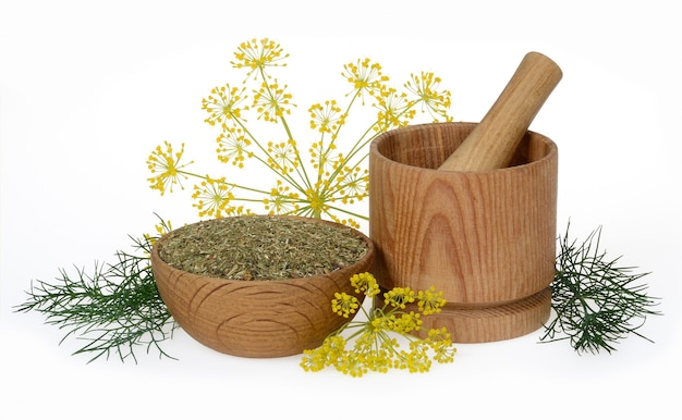 Dried dill crushed in a wooden bowl and a mortar on a white background