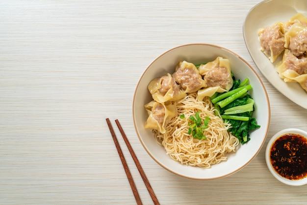ポークワンタンまたはスープなしのポーク餃子を添えた乾燥卵麺アジア料理スタイル