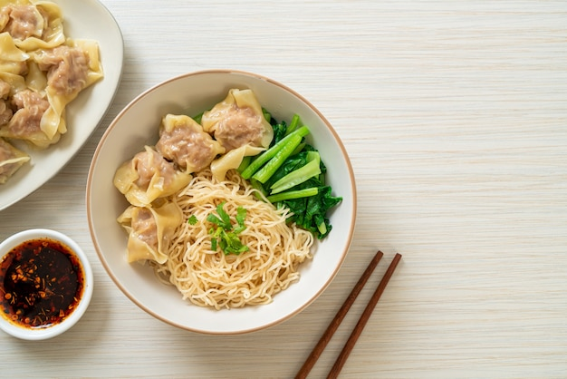 Dried egg noodles with pork wonton or pork dumplings without soup asian food style