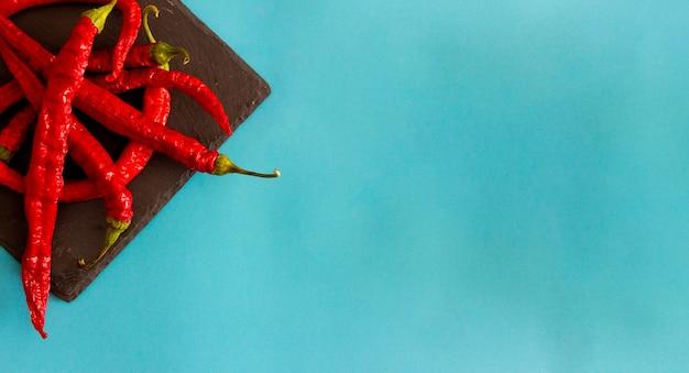 青い背景のスレートトレイに乾燥した細長い赤唐辛子。上面図。フラットレイ。スペースをコピーします。