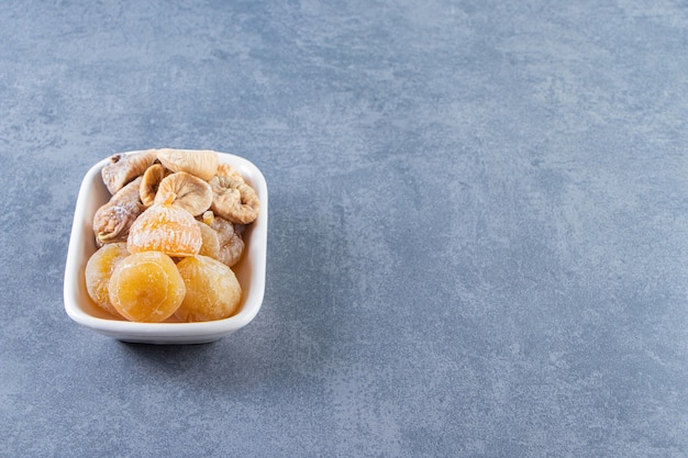 Dried figs in a bowl on the marble surface