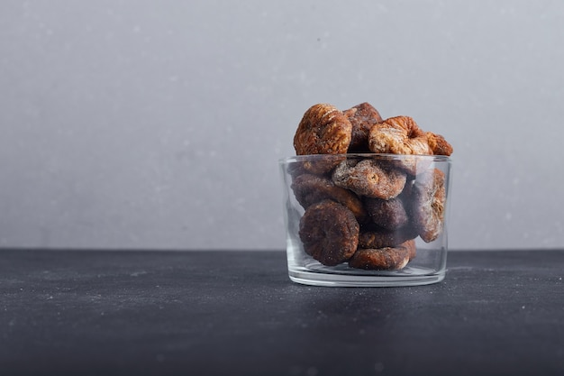 Dried figs in a glass cup on grey background.