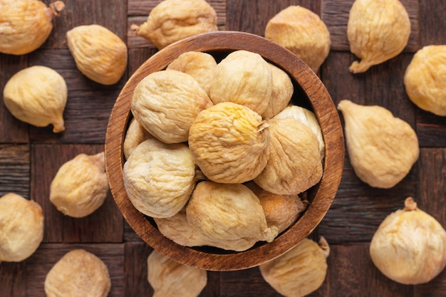 Dried figs in wooden bowl, top view.