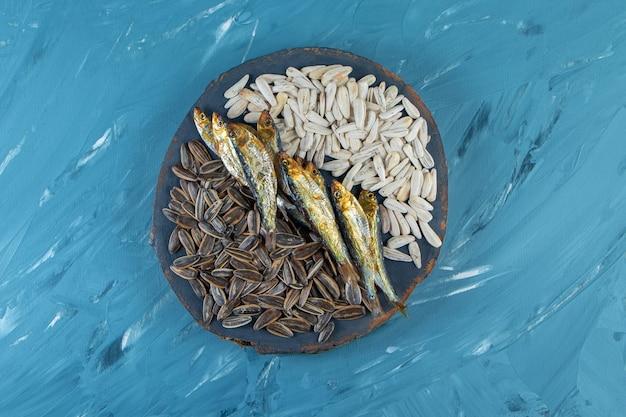 青い表面のボード上の干物と穀粒。