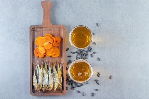 Dried fish and bread chips on a board next to glass of beers , on the marble background.