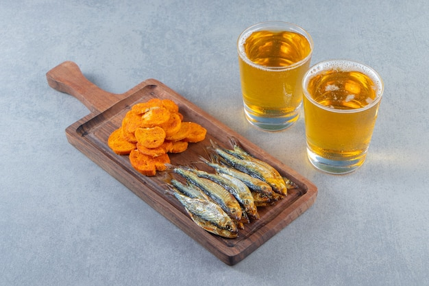 Dried fish and bread chips on a board next to glass of beers , on the marble surface.