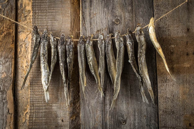 Dried fish hanging on a line on old boards