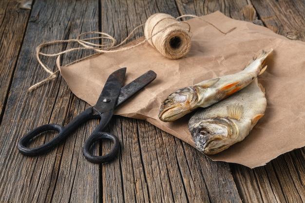 테이블에 말린 생선. 어두운 나무 배경에 짠 마른 강 물고기