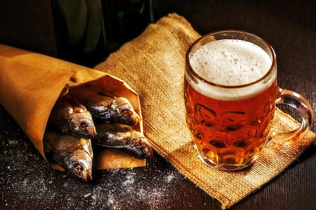 Dried fish and vintage glass of beer on dark wooden table