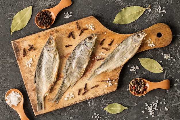 Dried fish with salt and pepper on cutting board