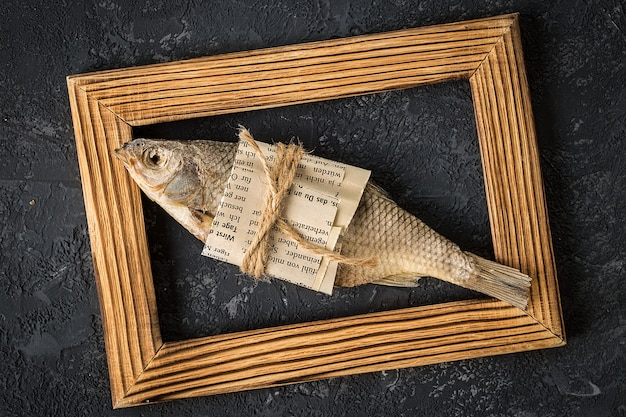 Dried fish in a wooden frame on a dark