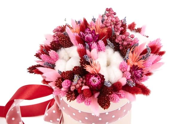 흰색 배경에 격리된 분홍색 둥근 모자 상자에 풀을 넣은 말린 꽃 꽃다발