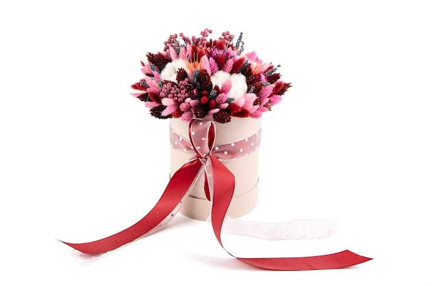 Dried flower bouquet with grasses in pink round hat box isolated on white background