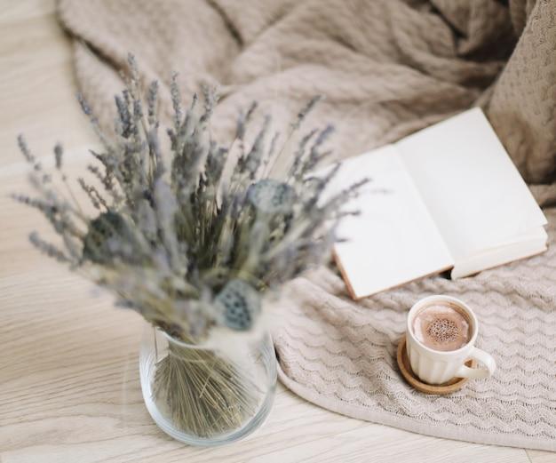 Сухие цветы и чашка капучино с книгой на деревянном фоне, вид сверху
