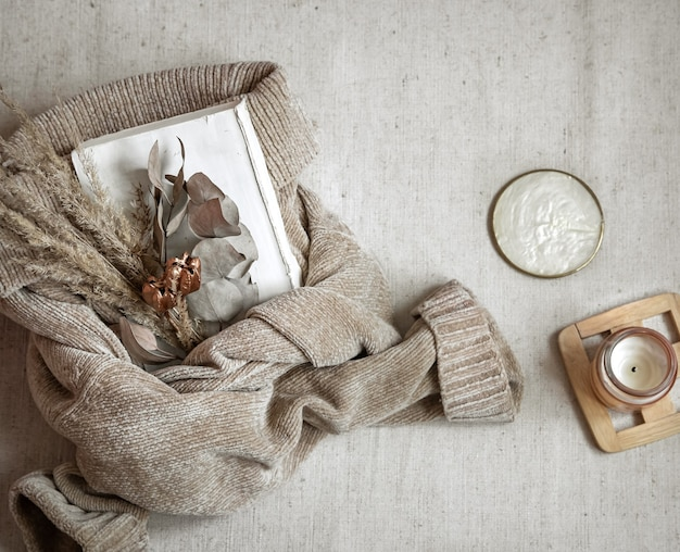 따뜻한 파스텔 스웨터와 촛불 평면도, 가을 아늑함 개념에 말린 꽃 꽃다발.