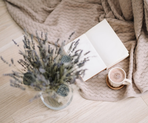 Dried flowers and a cup of cappuccino with book on wooden background. top view. flatlay