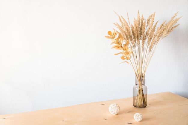 빈 빛 벽과 유리 꽃병에 말린 꽃