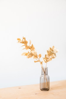 Сухие цветы в стеклянной вазе с пустой светлой стеной