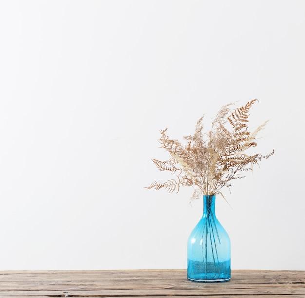 흰색 바탕에 나무 테이블에 파란색 유리 꽃병에 말린 꽃