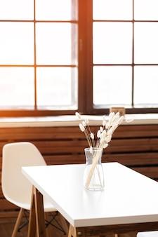 白いテーブルの上のガラスの瓶にドライフラワー。光沢のある窓の前のテーブルの上の花瓶に白いドライフラワー。