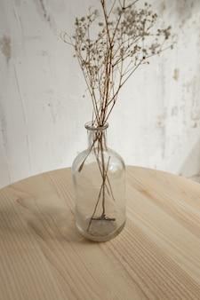 Сухие цветы в стекле на деревянном столе