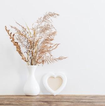 白い背景の上の木製のテーブルに花瓶のドライフラワー
