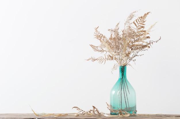 白い背景の上の木製のテーブルの花瓶のドライフラワー
