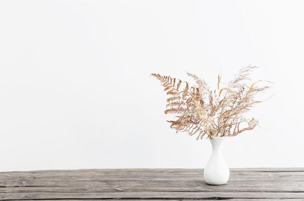 흰색 바탕에 나무 테이블에 꽃병에 말린 꽃