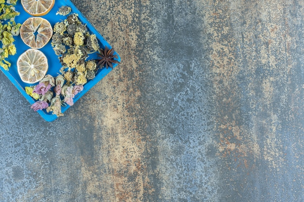 Fiori secchi e fette di limone sul piatto blu.