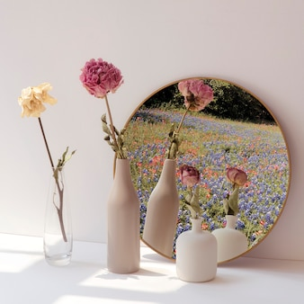 Dried flowers in minimal vases by a round mirror