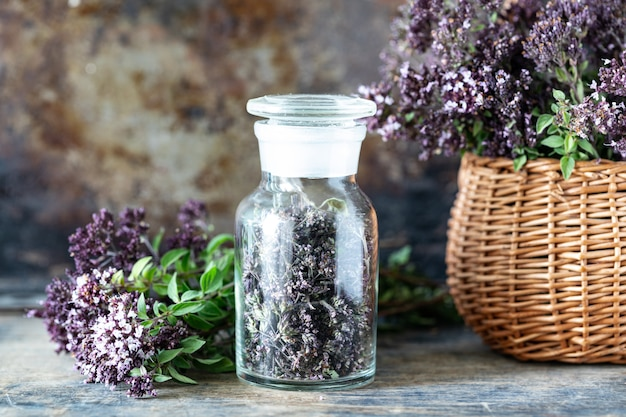 Dried flowers of oregano in a glass bottle on a wooden table.