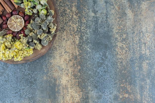 Сухие цветы, шиповник и корица на деревянном куске.