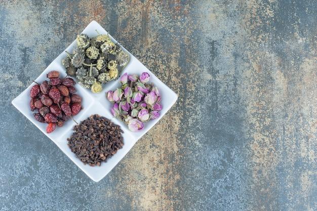 Fiori secchi, cinorrodi e chiodi di garofano sul piatto bianco.