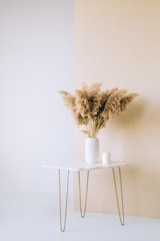 대리석 테이블, 흰색과 베이지 색 배경, 홈 인테리어 미니멀 한 에스테틱에 흰색 꽃병에 말린 꽃 spikelets 팜파스