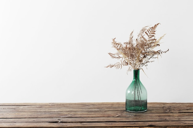 Dried flowers in vase on wooden table on white background