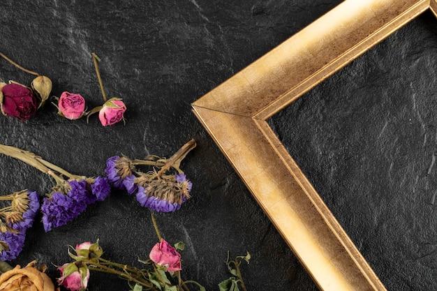 검은 테이블에 프레임이 있는 말린 꽃.