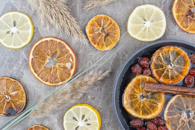 Fette di limone essiccate e fresche con cannella sulla superficie della pietra.